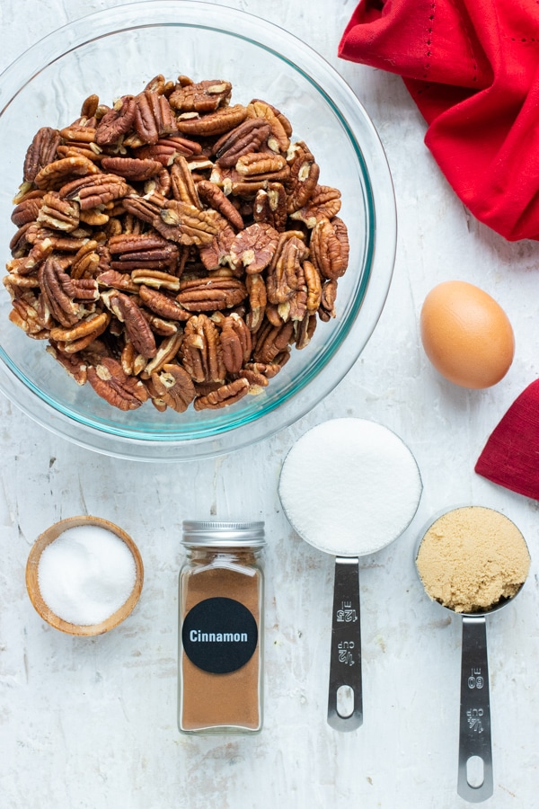 Pecans, cinnamon, sugar, and an egg as the ingredients for an easy, gluten-free candied pecans recipe.