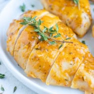 Honey mustard baked chicken breasts on a white dinner plate.
