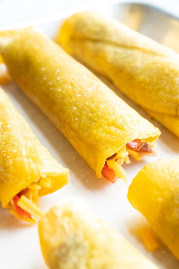 A close-up of how to roll taquitos and place on a baking sheet.