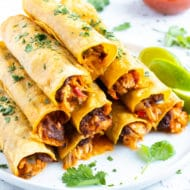 A stack of baked chicken taquitos with refried beans and cheese on a white plate for a Cinco de Mayo party.