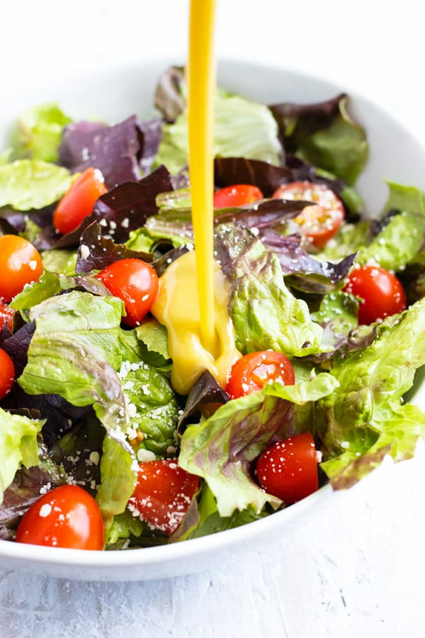 Honey mustard dressing being poured onto a salad with mixed greens and tomatoes.