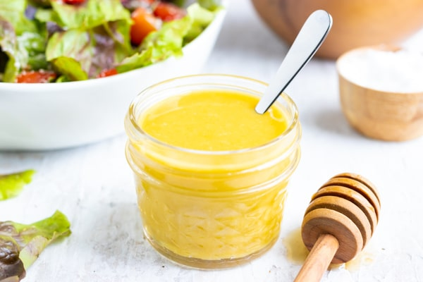 A small glass container that is full of mustard vinaigrette with a silver spoon.