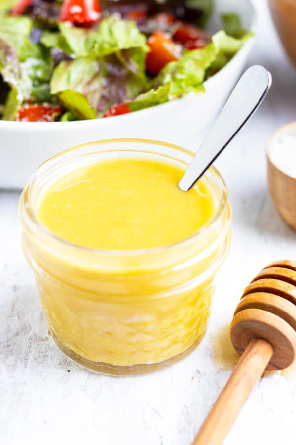 A clear container full of a healthy salad dressing made of honey and mustard.
