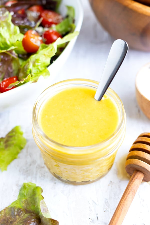 A jar full of honey mustard dressing with a silver spoon next to two wooden salad bowls.