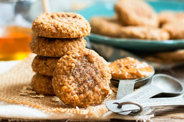 A stack of and easy oatmeal cookie recipe with measuring spoons next to them.