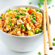 A white bowl full of chicken fried rice recipe with a pair of chopsticks.