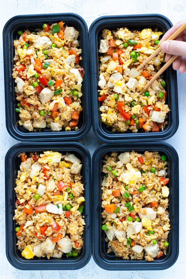 Meal prep containers full of chicken fried rice and a hand picking up some with chopsticks.