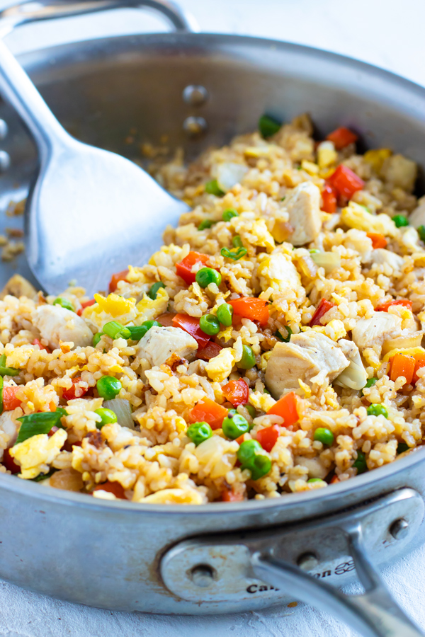 A skillet full of a quick and easy fried rice recipe with a metal spatula.