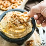 A hand dipping a pretzel into a bowl of hummus made with a gluten-free lentil recipe.