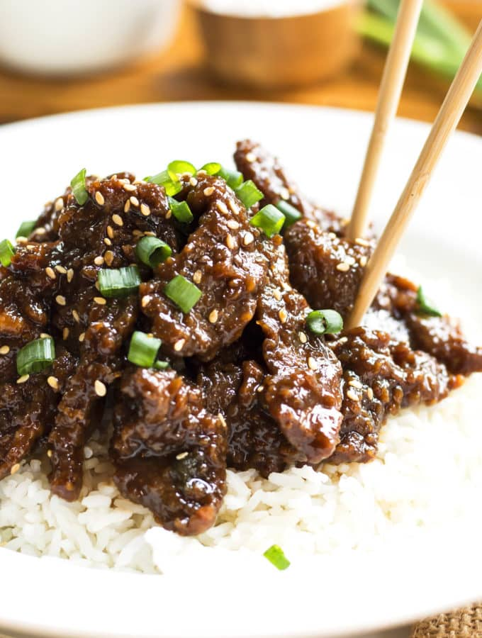 Copycat PF Chang's Mongolian Beef on a bed of rice with chopsticks for lunch.