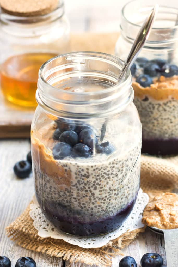 A chia seed pudding recipe inside a jar filled with peanut butter and blueberries for a healthy breakfast.