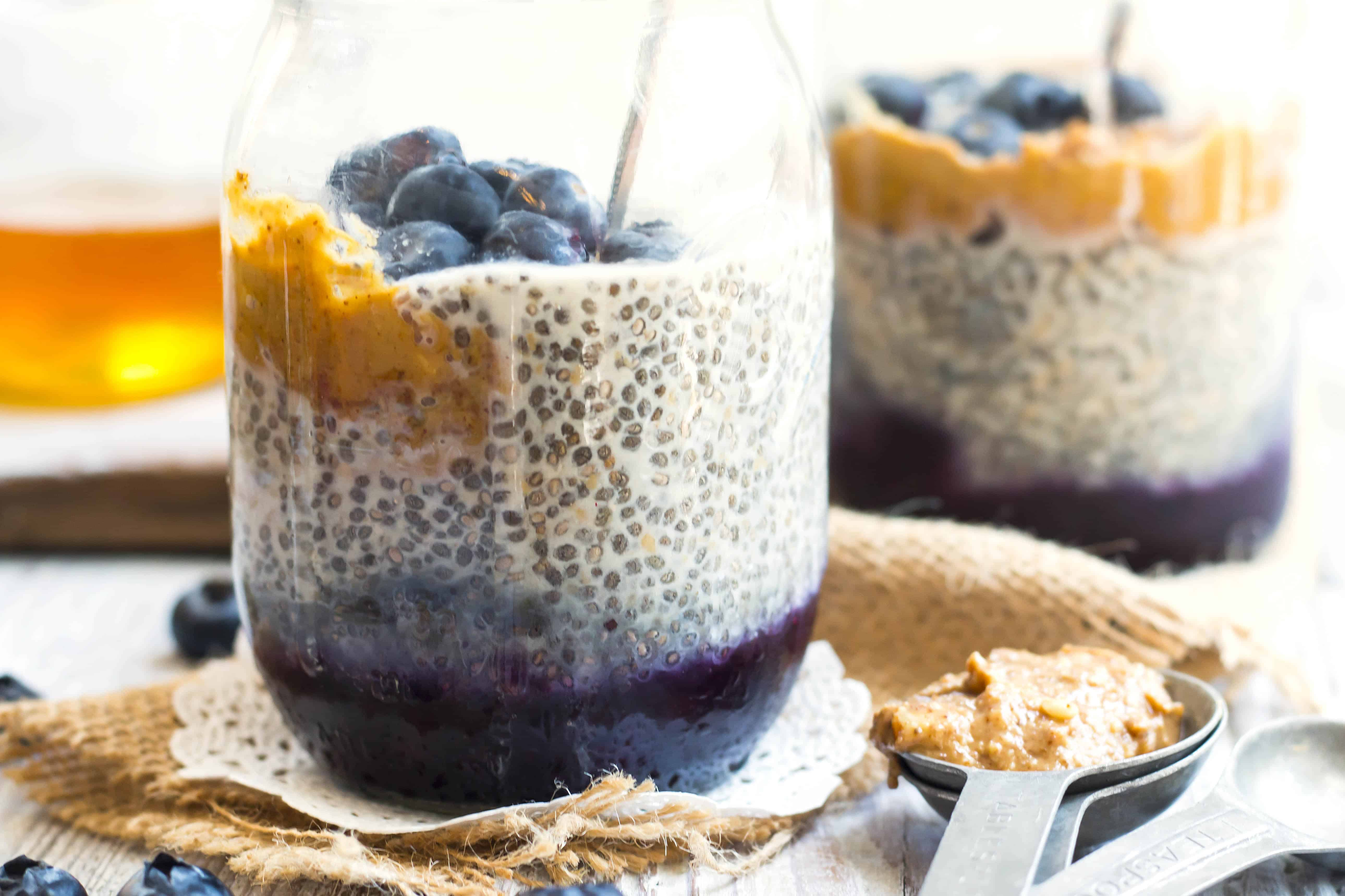 A jar filled with gluten-free chia seed pudding with peanut butter and jelly for a healthy breakfast.