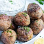 Low-carb and gluten-free meatballs are served plain as a dinner or an appetizer with a creamy, greek sauce.
