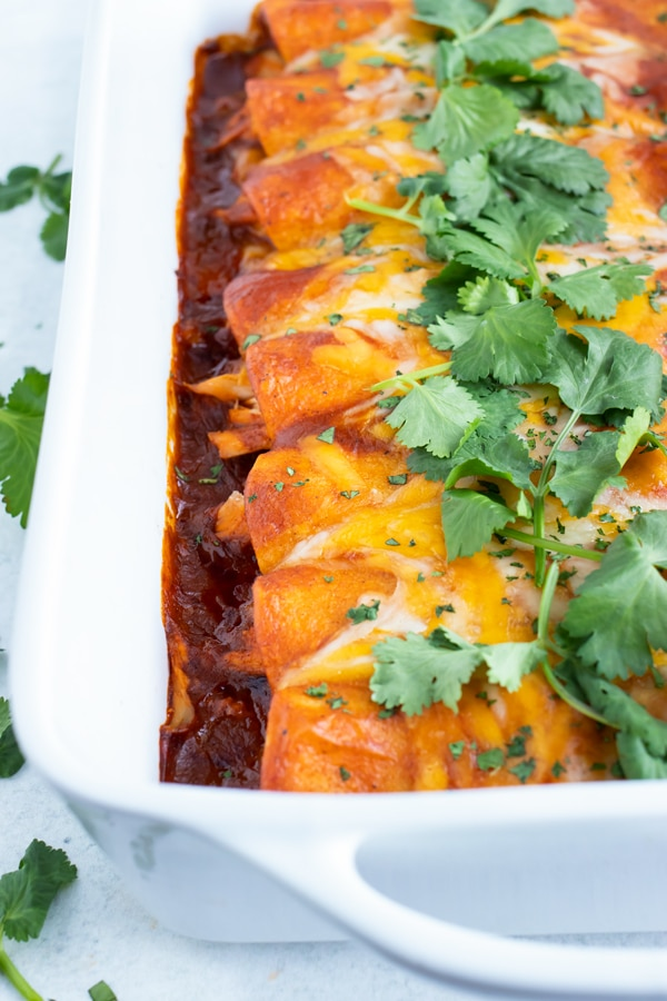A white casserole dish full of shredded chicken enchiladas with cilantro on top.