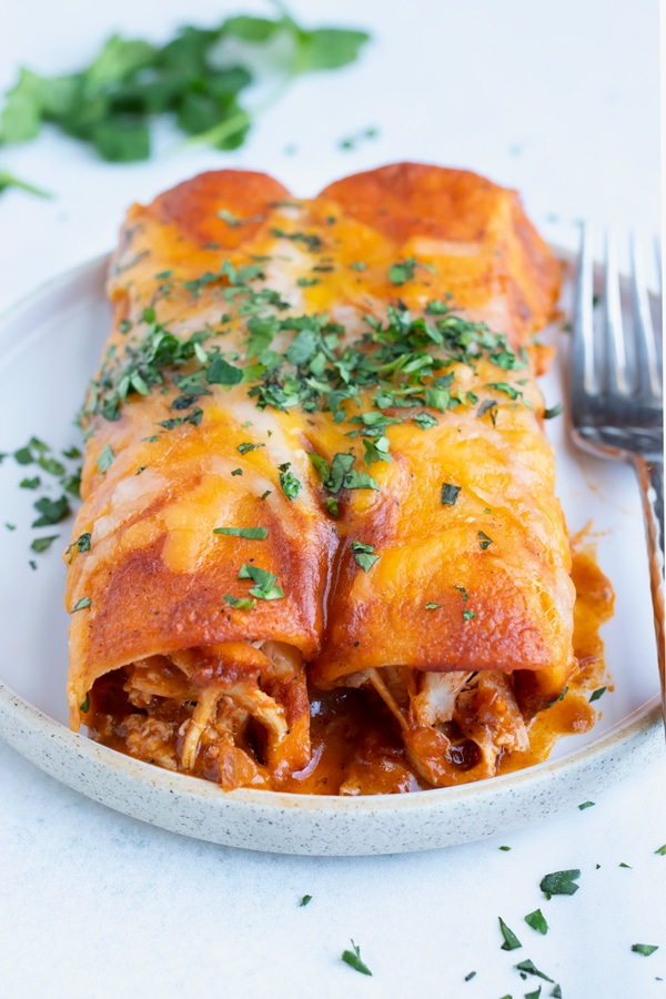 Authentic Mexican cheesy chicken enchiladas with homemade sauce and cilantro on top.