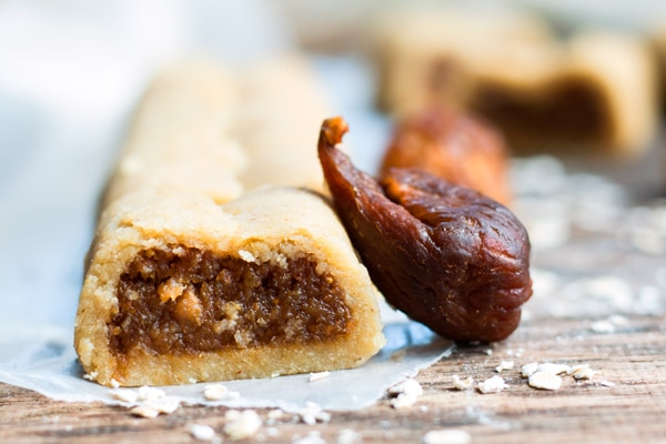 A gluten-free fig newton recipe on a piece of parchment paper with a fig on the side.