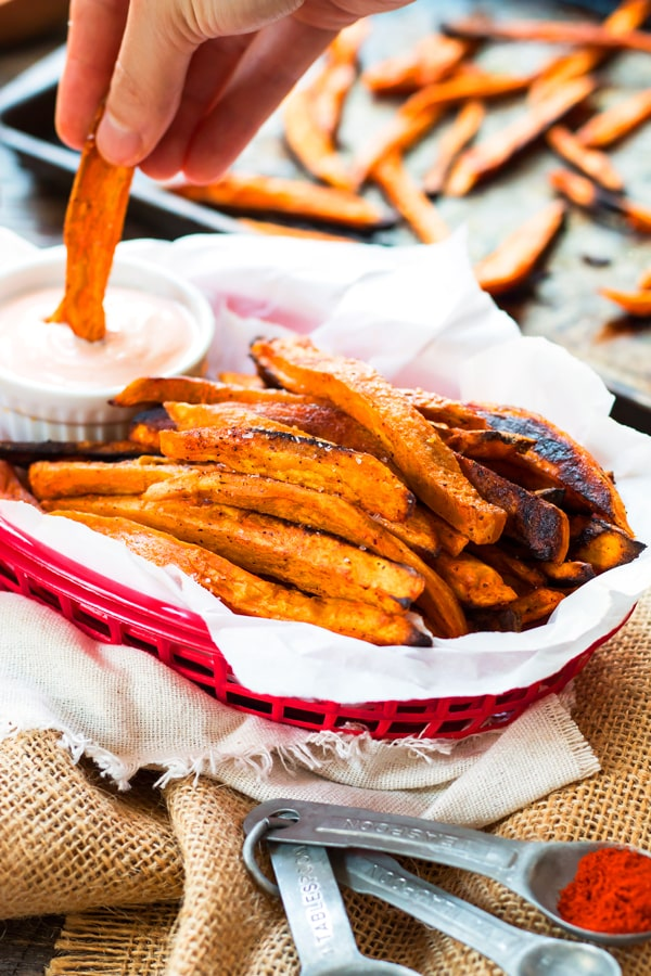 Oven-Baked Sweet Potato Fries with Sriracha Mayo | A crispy and healthier sweet potato fries recipe with paprika. They're baked in the oven, not fried, and served with a spicy sriracha mayo.