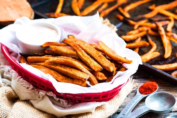 A basket of fries made with a sweet potato recipe served with spicy Sriracha mayo.