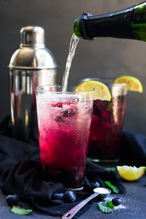 A blueberry champagne cocktail that is full of fresh lime juice, mint, and rum. It makes a wonderful party drink for birthday parties, holiday parties, New Year's Ever or any special occasion.