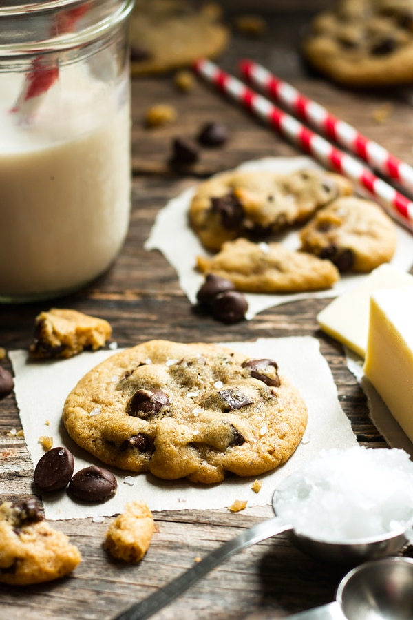 Chocolate chip cookies on a table with a glass of milk for a healthy dessert.