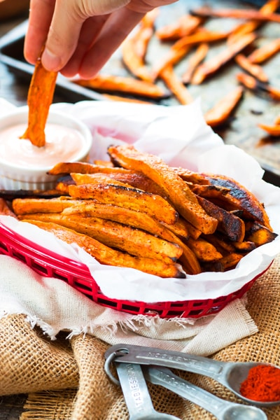 A hand dipping a gluten-free sweet potato fry in Sriracha mayo for a quick snack.