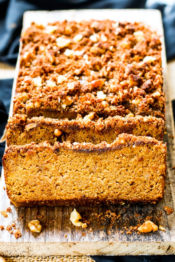 A sliced loaf of gluten-free, healthy pumpkin bread on a piece of wood.