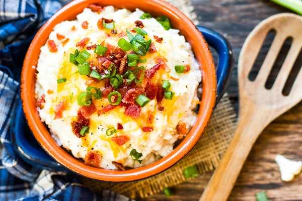 An overhead picture of loaded cauliflower mashed potatoes in a blue bowl with a wooden spoon on the side.