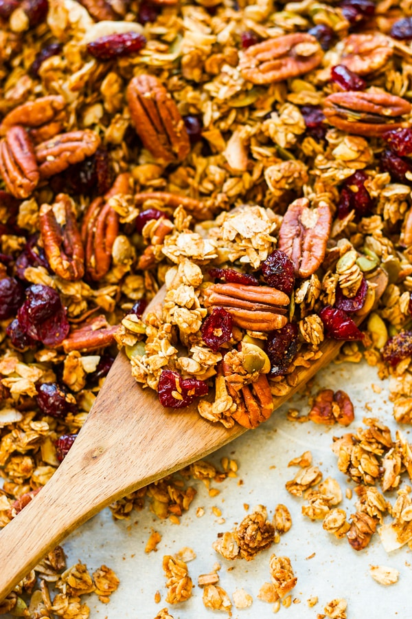 A wooden spoon filled with a gluten-free granola recipe ready for a healthy breakfast.