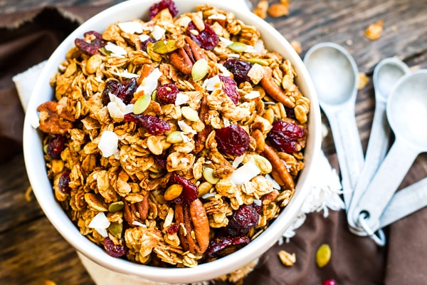 A bowl of gluten-free Pumpkin Granola with Maple Syrup on a table for a healthy breakfast.