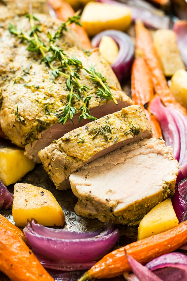 A pork tenderloin recipe surrounded by apples and vegetables for a healthy dinner.