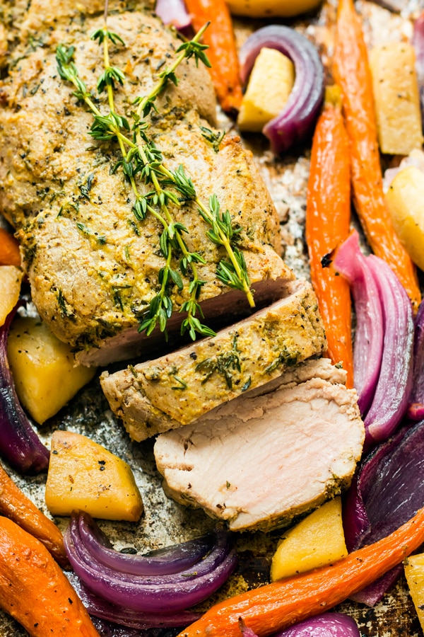 A mustard pork tenderloin sliced into two pieces and surrounded by vegetables.