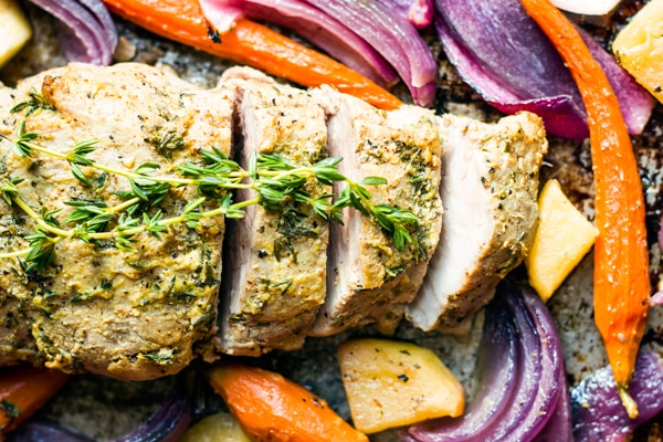 Gluten-free pork tenderloin with apples sliced into four pieces on a baking sheet.