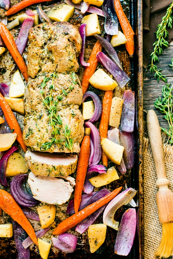 Gluten-free Roasted Pork Tenderloin made with mustard on a baking sheet surrounded by vegetables.