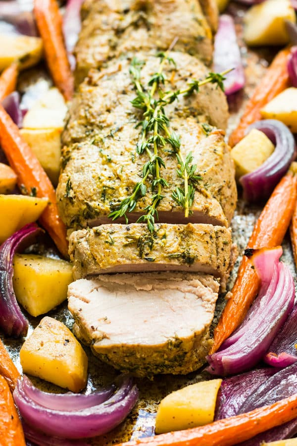 Roasted Pork Tenderloin with Mustard, Apple, and Vegetables on a baking sheet for an easy dinner.