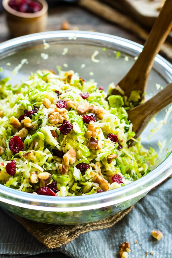 Gluten-free Shredded Brussel Sprouts recipe in a bowl with two wooden serving spoons.