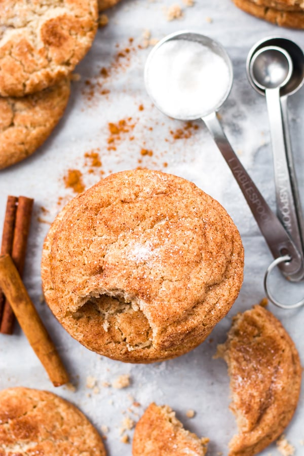 A stack of gluten-free snickerdoodles with a bite taken off the top.