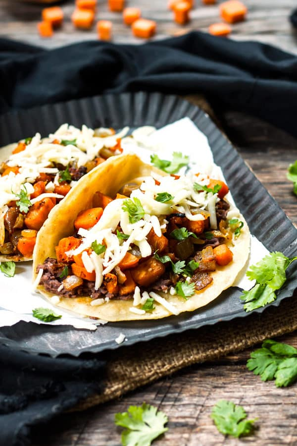 Black Bean & Sweet Potato Tacos | A gluten free and vegetarian taco full of refried black beans, sweet potatoes, cilantro and cheese! They make a great breakfast, lunch or dinner taco recipe.