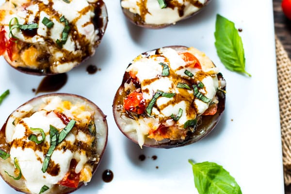 Gluten-free potato skins stuffed with mozzarella, basil, and tomatoes with a balsamic drizzle.
