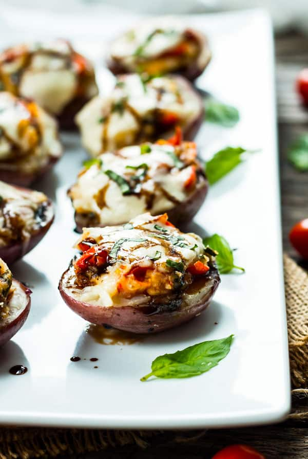 A line of Caprese Stuffed Baked Potato Skins surrounded by fresh basil for a healthy appetizer.
