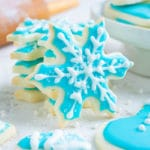 Cut-out sugar cookies in the shape of snowflakes for a Christmas party dessert.
