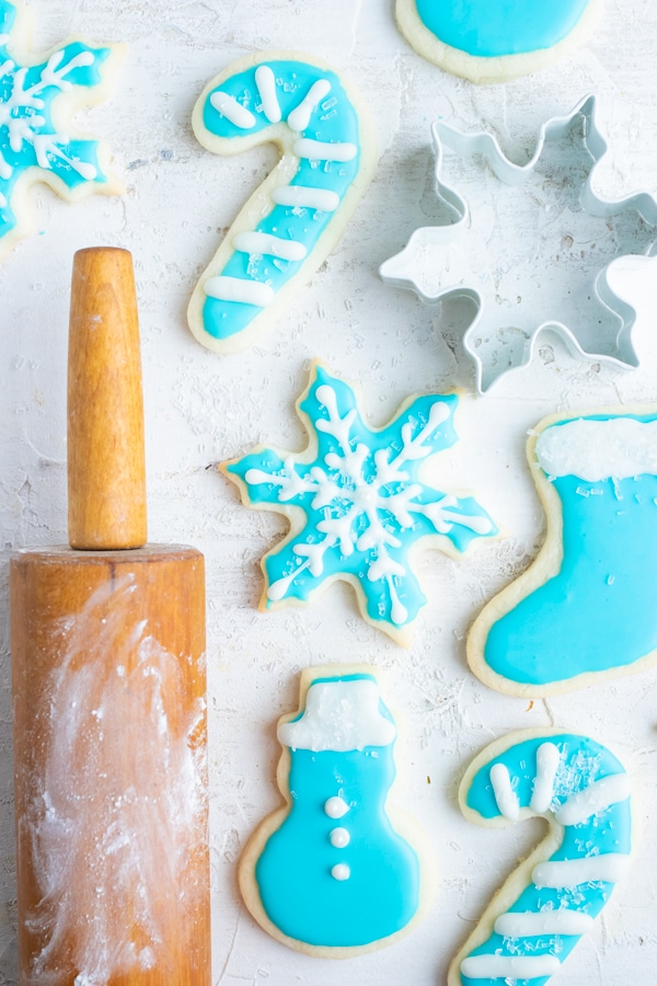 Gluten-free Christmas sugar cookies next to a cookie cutter and a rolling pin with powdered sugar.