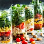 A line of mason jar lunches using fresh vegetables and other ingredients.