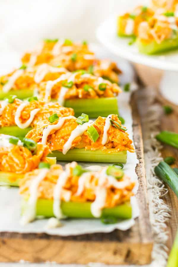 A collection of Buffalo Chicken Celery Sticks with ranch dressing drizzled on top.