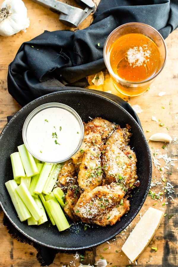 Easy baked chicken wings with Parmesan and garlic sauce in a black bowl with celery, Ranch dressing, and a beer next to it.