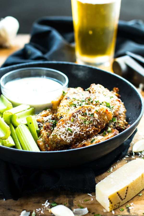A black bowl full of a baked chicken wings recipe with Parmesan and garlic.