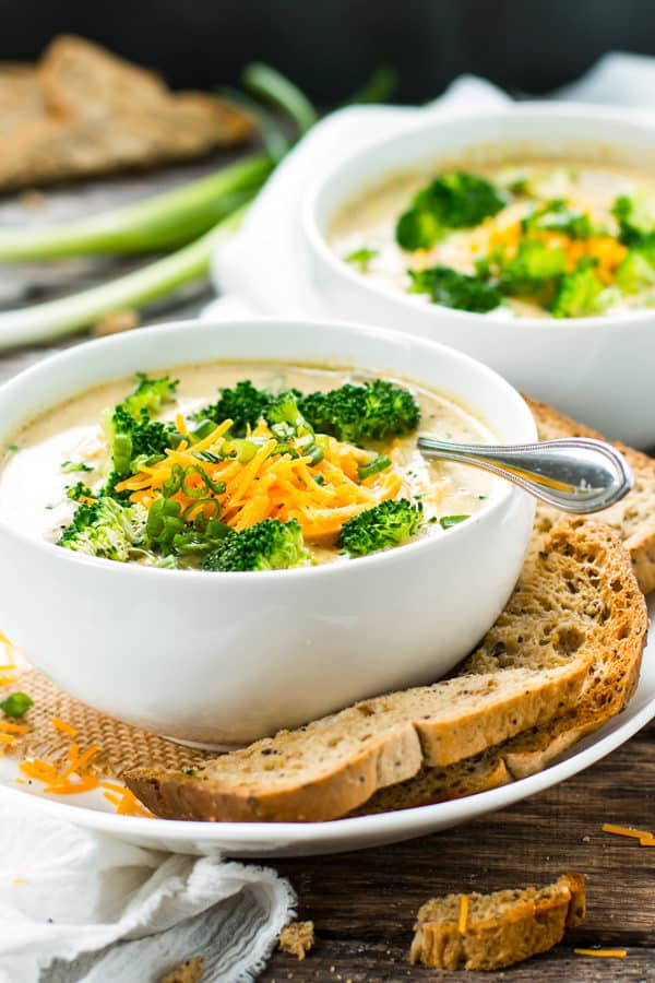 Broccoli cheddar soup in a bowl with garlic bread surrounding it.