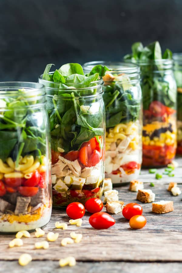 A line of gluten-free mason jar salad recipes on a table ready to eat for a healthy lunch.