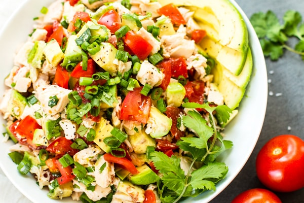 A close up picture of chicken avocado salad in a white bowl with whole tomatoes on the side.