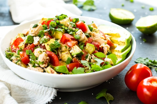 Healthy avocado chicken salad with tomatoes in a white bowl for a light dinner.