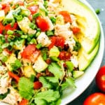 Gluten-free avocado chicken salad recipe in a bowl with tomatoes for a healthy lunch.